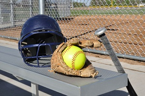 softball in glove on a bench with bat and helmet